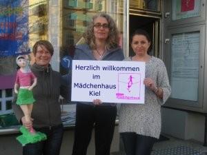 """Drei Mitarbeiterinnen der Mädchenhaus-Beratungsstelle stehen vor dem Schaufenster der Beratungsstelle und zeigen ein Schild mit der Aufschrift """"Herzlich Willkommen im Mädchenhaus Kiel"""""""