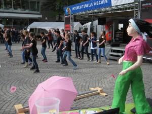 Der Infostand des Mädchenhaus Kiel auf den Interkulturellen Wochen 2013, im Hintergrund tanzt eine Gruppe Jugendliche vor einer Bühne