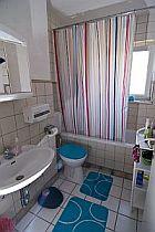 Das badezimmer in der Mädchen-WG mit weißen Fliesen, einem buntgestreiften Duschvorhang, blauem Teppich