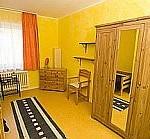 Blick in ein Mädchenzimmer in der Mädchen-WG mit gelb gestrichener Wand , Holzspiegelschrank, Stuhl und Teppich