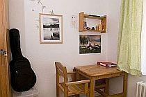 Blick in ein Mädchenzimmer in der Zufluchtsstätte mit Tisch, Stuhl, Bildern an der Wand und Gitarre.