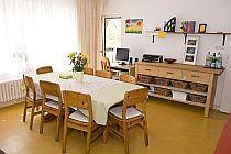 Das Esszimmer der Zufluchtsstätte des Mädchenhauses Kiel hat ein großes helles Fenster und einen Tisch mit 8 Stühlen