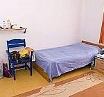 Ein Mädchenzimmer in der Zufluchtsstätte mit Bett, Teppich, Stuhl und Regal