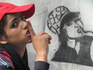 Sonita trägt ein rotes Cappy, steht vor einer Mauer, auf der sie als Graffiti zu sehen ist