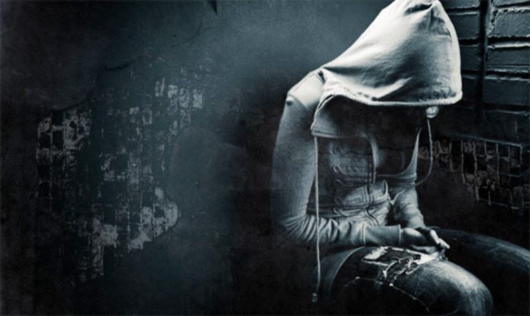 Mädchen mit Kapuzenshirt und zerfetzter Jeans sitzt mit hängendem Kopf vor einer dinklen Steinwand mit Graffitis