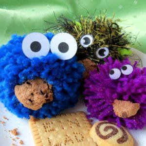 Einladung zum Offenen Mädchenhaus-Café Vorderseite zeigt 3 Bommelmonster mit Keksen