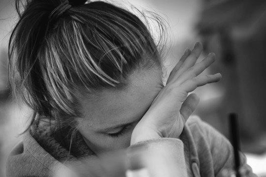 Bild einer jungen Frau, die sich traurig mit dem Handrücken über die Augen wischt