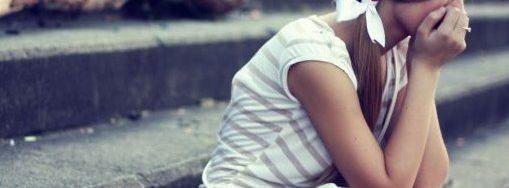 Teenager-Mädchen mit langen braunen Haaren sitzt auf Steintreppe. Sie hat das Gesicht auf die Hände gestützt und sieht traurig aus.